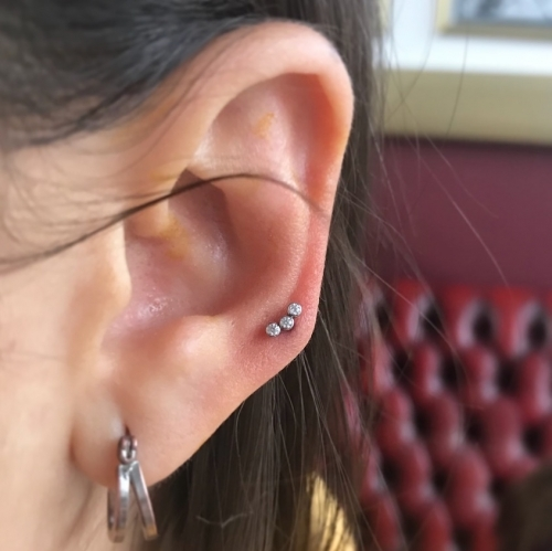 High lobe piercing by Mara, installed with a Swarovski crystal cluster from I.S