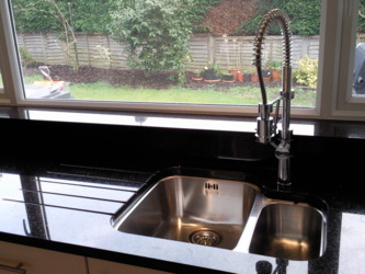 Absolute black granite worktops showing under mounted sink and drainage grooves.Black kitchen worktops Lightwater Surrey