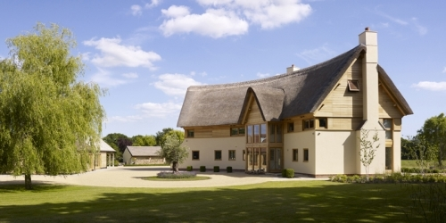 A modern vernacular house in the New Forest, Hampshire, taking advantage of sustainable technologies such as air source heat pumps and passive solar gain through the curved plan design and building orientation