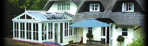 White painted oak conservatory on thatched cottage